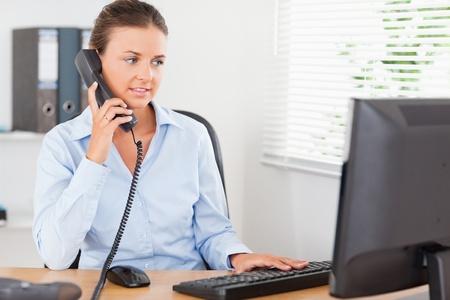 Retrato de una mujer de negocios hermosa en el teléfono en la oficina Foto de archivo
