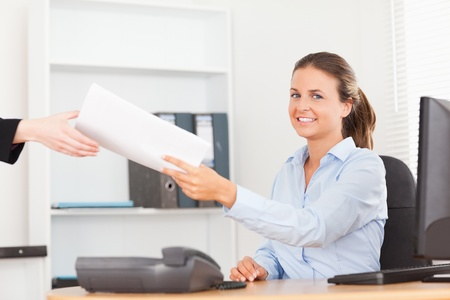 smiling businesswoman receiving a pile of paper looking into the camera in her office photo