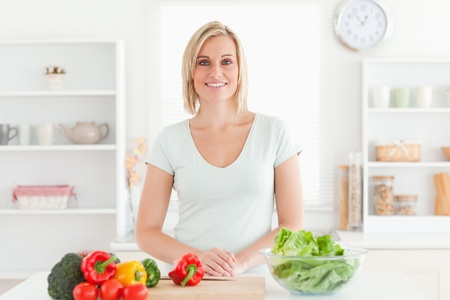 Woman standing in kitchen with vegetables photo