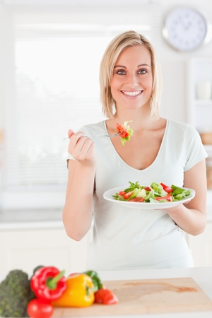 Woman eating salad in the kitchen photo
