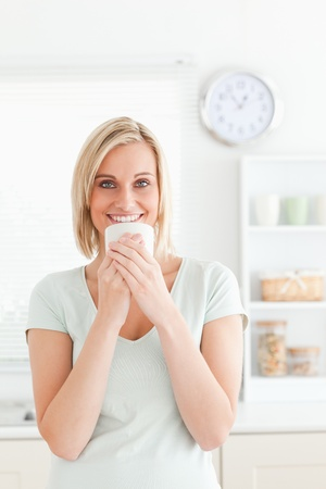 Woman holding cup of coffee in the kitchen photo