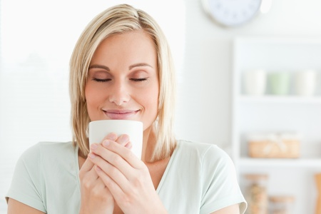 Close up of a woman taking in smell of coffee with her eyes closed in the kitchen photo