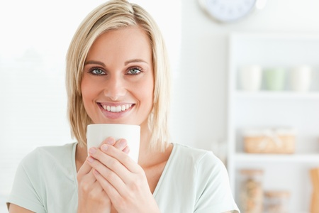 Close up of a woman taking in smell of coffee looking into the camera in the kitchen photo