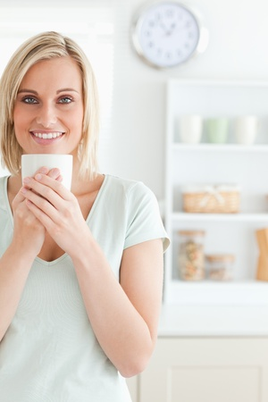 Portrait of a woman taking in smell of coffee looking into the camera in the kitchen photo