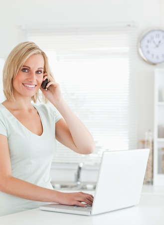 calling: Blonde woman with a laptop and a phone looking into the camera in the kitchen