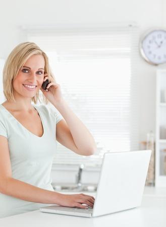 calling: Mujer rubia con un ordenador port�til y un tel�fono mirando a la c�mara en la cocina Foto de archivo