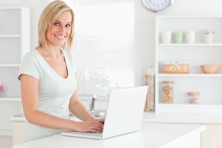 Charming woman with a laptop looking into the camera in the kitchen Stock Photo - 11199924
