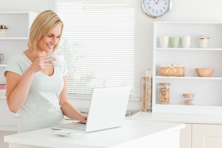Woman with a cup of coffee and a laptop in the kitchen photo