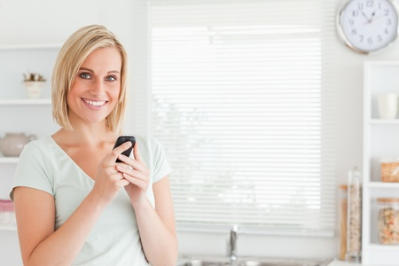 Charming woman with a mobile looking into the camera in the kitchen photo