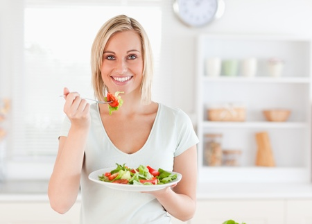 ätande: Närbild på en vacker kvinna äter sallad i köket