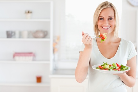 Close up of a cute woman eating salad in the kitchen photo