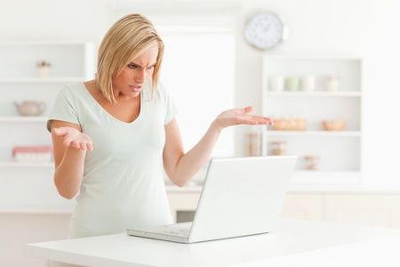clue: Woman looking at notebook in the kitchen without having any clue what to do  Stock Photo