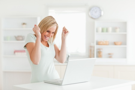 Laughing charming woman looking at laptop in the kitchen photo