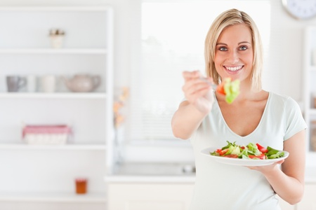Close up of a good looking woman eating salad in her kitchen photo