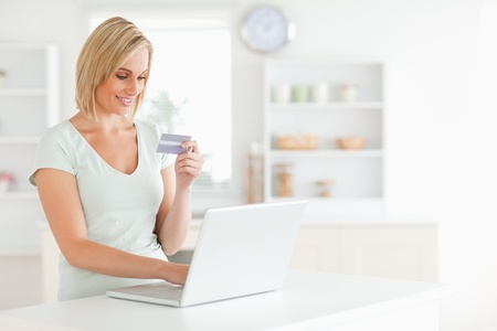 Woman with credit card and notebook in the kitchen photo