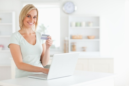 room card: Woman with credit card and notebook looks into camera in the kitchen Stock Photo