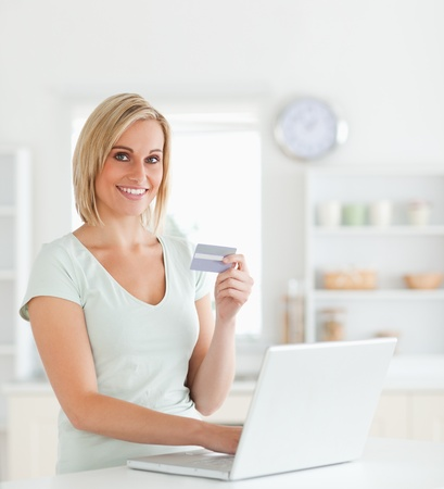 Blonde woman with credit card and notebook looks into camera in the kitchen photo