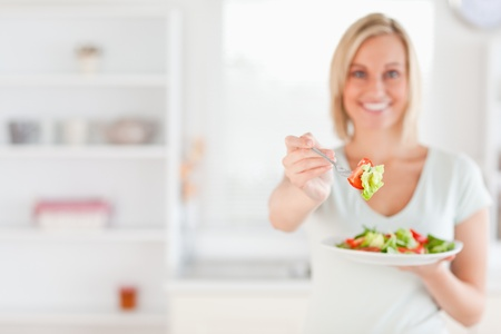 Woman offering salad in her kitchen photo