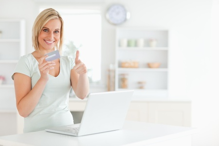 Blonde woman with credit card and notebook holding thumb up in the kitchen photo