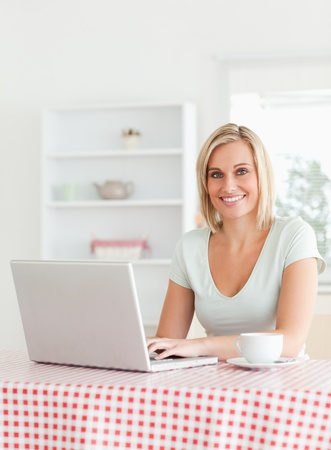 Smiling woman sitting at a kitchen table with cup of coffee and notebook looking into the camera photo
