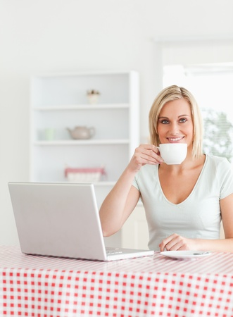 Woman drinking coffee with notebook in front of her in the kitchen photo