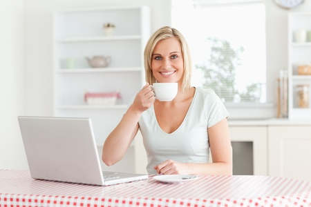 Woman drinking coffee with laptop in front of her looking into the camera in the kitchen photo