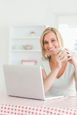 Close up of a woman holding cup of coffee with laptop in front of her smiling at camera in the kitchen photo