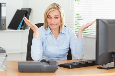 Young blonde woman sitting behind desk not having a clue what to do next in an office photo