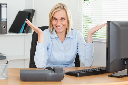Smiling blonde woman sitting behind desk not having a clue what to do next in an office photo