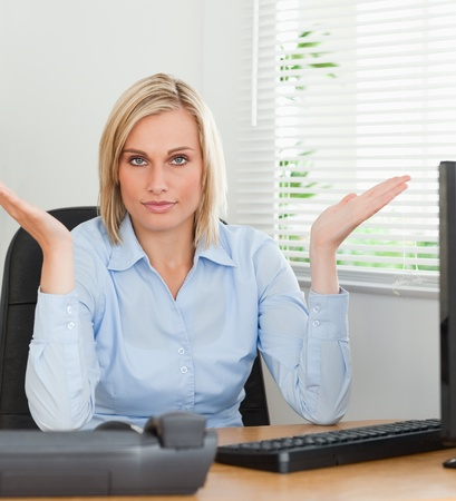 Serious woman sitting behind desk not having a clue what to do next in an office photo