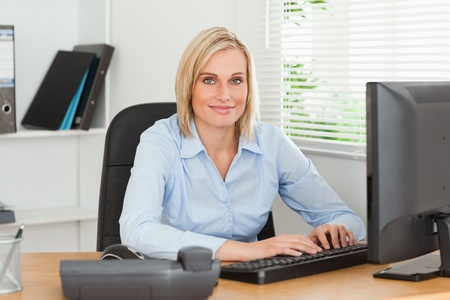 Working woman in front of a screen looks into camera in an office photo