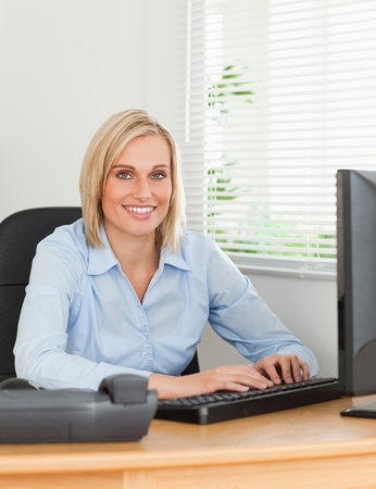 Working blonde woman in front of a screen looks into camera in an office photo