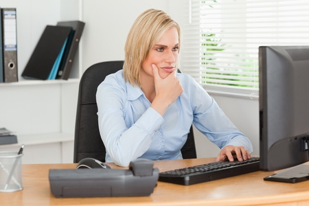 Working thoughtful woman in front of a screen looking at it in an office  photo