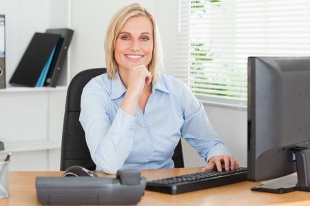 looking into camera: Lavorare donna carina di fronte a uno schermo guardando la telecamera in un ufficio