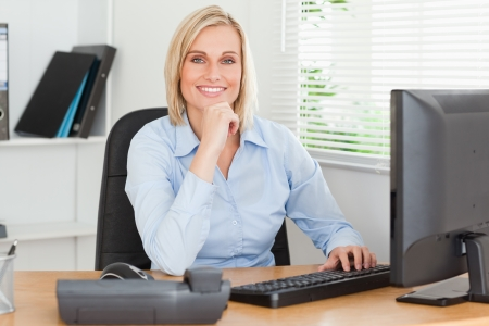 woman office: Working cute woman in front of a screen looking into camera in an office