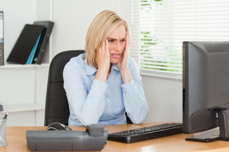 Frustrated working woman in front of a screen in an office photo