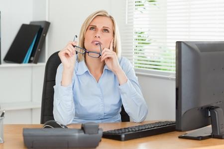 mujeres pensando: Mujer pensativa con gafas en una oficina