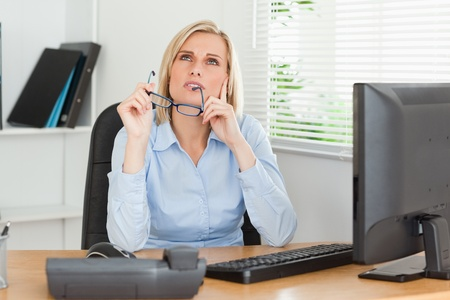 Thoughtful woman with glasses in an office photo