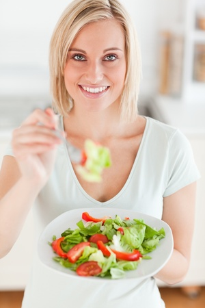 Cute woman offering salad in the kitchen photo