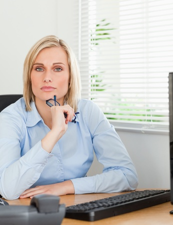 Serious thoughtful looking woman behind her desk looking into camera in her office photo
