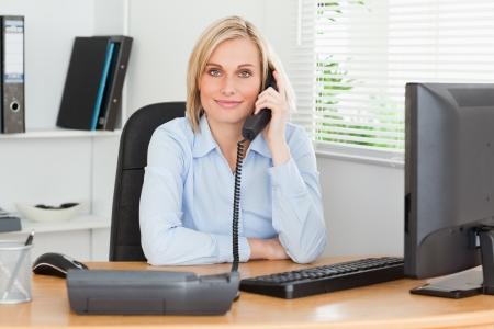 hablando por celular: Sonriendo empresaria en el teléfono en su oficina