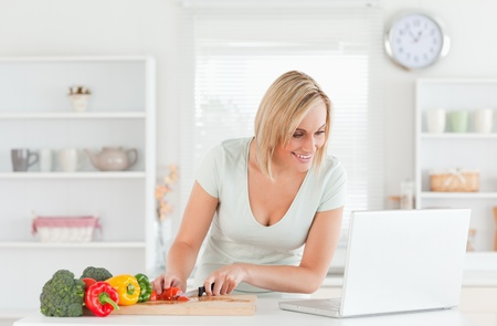 Woman looking for a recipe on laptop in the kitchen photo