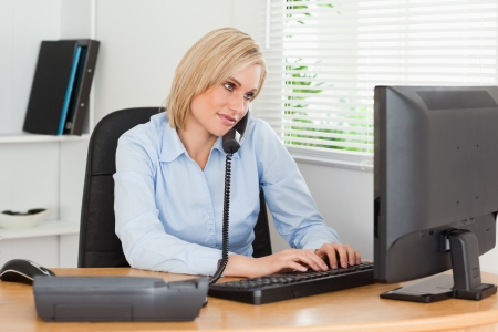 Working businesswoman in her office on the phone while typing photo