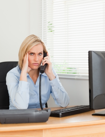 Blonde businesswoman on phone while having headache looks into camera in her office photo