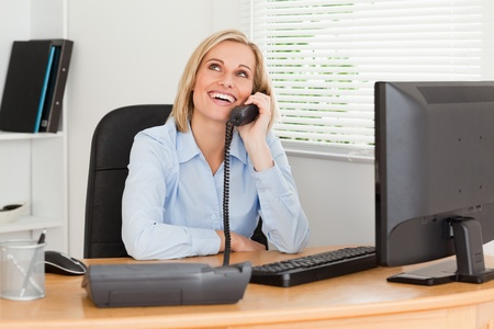 Cheerful businesswoman on phone looking at the ceiling of her office photo