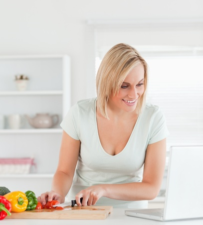 Close up of a young woman looking for a recipe on laptop in the kitchen photo