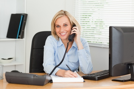 lady on phone: Cute businesswoman on phone writing something down looks into camera in her office