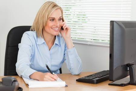 Cute blonde businesswoman on mobile writing something down looks at her screen in her office photo