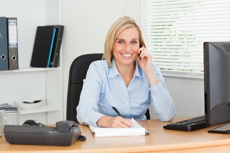 Cute businesswoman on mobile noting something looks into camera in her office photo
