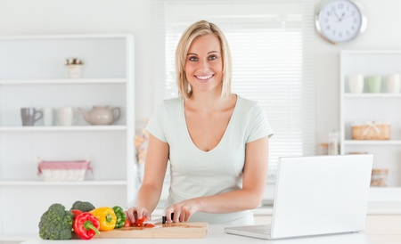 Close up of a young woman looking into camera while cutting peppers in kitchen photo